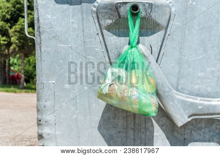 Pieces Of Bread In The Plastic Or Nylon Bag Left On The Metal Garbage Dumpster Can On The Street In