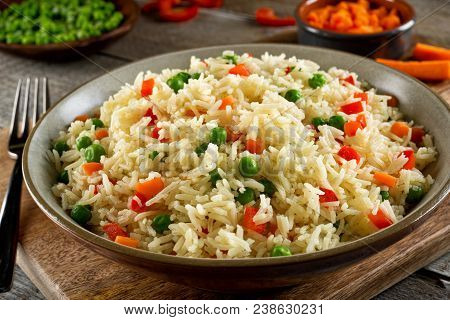 Delicious Vegetable Rice Pilaf With Green Peas, Carrots And Red Peppers.