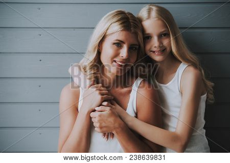 Blonde Cute Girl Hugs Blonde Mother On Wooden Background. Concept Of Relationship Between Mother And