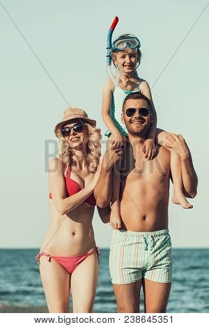 Happy Family In Swimsuits Has Fun Vacation On Ocean Coast. Young Couple With Daughter On Summer Vaca