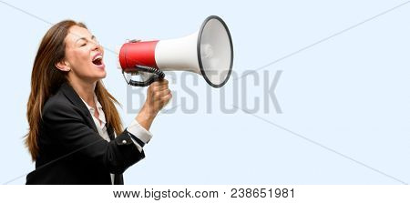 Middle age woman wearing jacket communicates shouting loud holding a megaphone, expressing success and positive concept, idea for marketing or sales isolated blue background