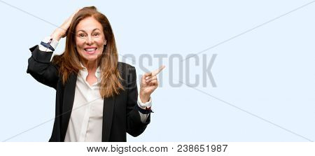 Middle age woman wearing jacket pointing away side with finger isolated blue background