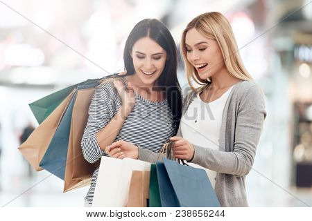 Young Girlfriends With Shopping Bags Are Shopping At Mall. Shopping Concept. Consumerism Concept. Sa