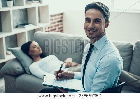 Portrait Of Psychologist Who Consulting A Woman In Office. Psychotherapy Concept.