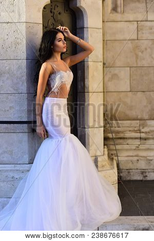 Sexy Girl In White Dress With Stylish Hair. Woman At Stone Ancient Column In Summer. Wedding Fashion