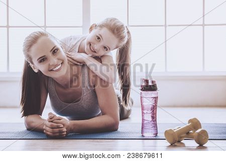 Beautiful Young Woman And Charming Little Girl Are Looking At Camera And Smiling While Lying On Yoga