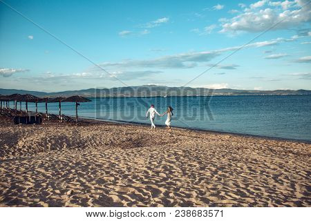 Man And Woman Hold Hands, Couple Happy On Vacation. Couple In Love Stand On Beach, Seashore. Honeymo