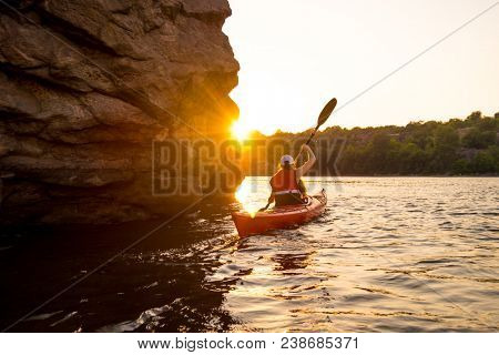 Young Woman Paddling the Red Kayak on the Beautiful River or Lake near High Rocks at Sunset
