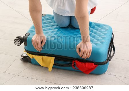 Young Woman Struggling To Close Suitcase Indoors