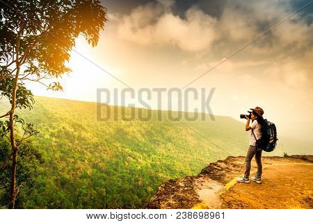 Young Traveling Woman With Backpack, Hat And Camera Stand On The Mountain Cliff. Female Photographer