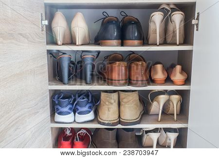 Close Up Fashionable Women High Heels, Leather Men Shoes And Sport Shoes In Wooden Cabinet For Going