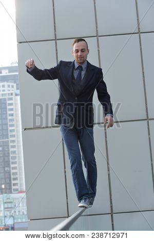 brave businessman walking along the abyss edge