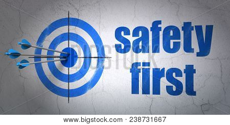 Success Protection Concept: Arrows Hitting The Center Of Target, Blue Safety First On Wall Backgroun