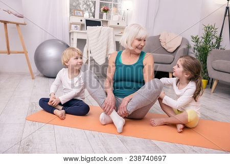 My Dear Grandchildren. Happy Grey-haired Woman Smiling And Exercising With Her Grandchildren