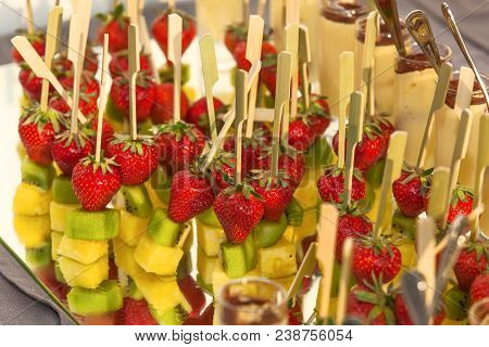 Canape On A Wooden Skewer With Strawberry, Kiwi And Pineapple On A Buffet For A Party Or Wedding, Ca