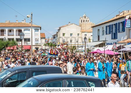 Saintes-Maries-de-la-Mer, France - May 25, 2015. Religious feast of the Holy Maries in Provence. The concept of ethnographic tourism. Huge crowd accompanies two statues Saintes-Maries