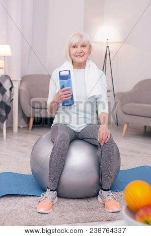 Vital Hydration. Cheerful Elderly Woman Sitting On The Balance Ball And Posing With A Bottle Of Wate
