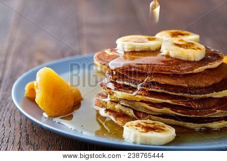 Homemade Pancakes With Honey, Apricot And Walnuts On Blueish Plate Over Rustic Wooden Background, Se