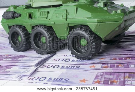 Close Up Green Tank Toy Placed On Euro Banknotes Pile. Business And Economy War. New World War From