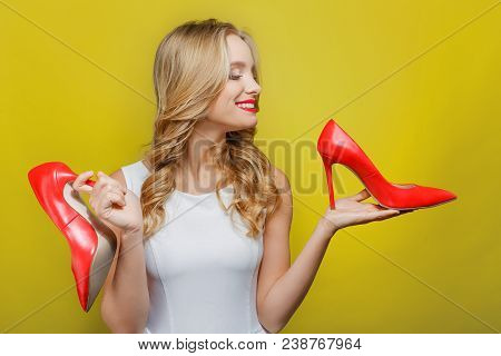 Awesome And Nice Girl Is Holding Red Shoes With High Heels In Her Hands. She Is Looking At One Of Th