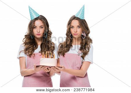 Attractive Young Twins Holding Birthday Cake And Looking At Camera Isolated On White