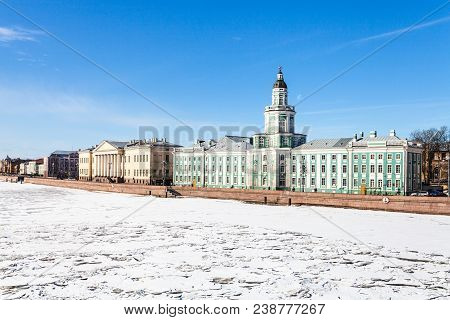 view of Universitetskaya Quay with Kunstkamera and Academy of Sciences buildings on Vasilievsky Island in St Petersburg city from the Palace Bridge in sunny march day poster