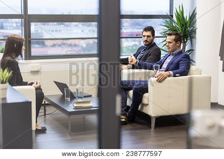 Businessmen Interviewing Female Candidate For Job In Modern Corporate Office. Woman During Job Inter