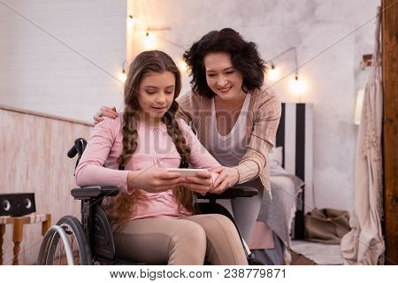 Modern Opportunities. Adorable Crippled Girl Using Smartphone While Woman Looking At Screen
