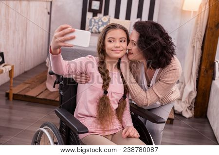 Charming Photo. Satisfied Crippled Girl Using Phone While Woman Kissing Her
