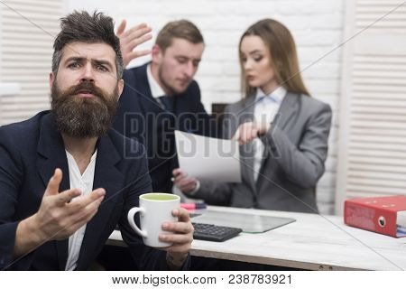 Man With Beard On Hopeful Face Holds Mug, Bosses, Coworkers, Colleagues On Background. Business Nego