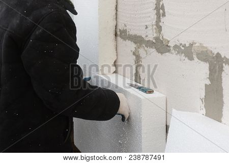 Builder Installing Rigid Styrofoam Insulation Board For Energy Saving. Rigid Extruded Polystyrene In