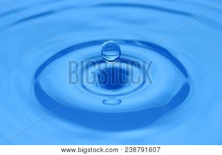 Water Drop Close Up On A Blue Surface. Abstract Backgrpound. Shallow Dof.