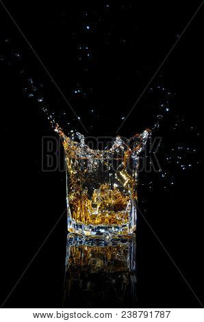 Whiskey With Splash On Black Background.