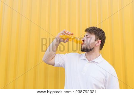 A Handsome Man Drinking An Orange Drink From A Bottle On The Background Of A Yellow Wall. A Young Ma