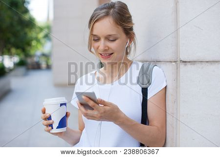 Portrait Of Happy Woman With Coffee Listening To Music On Phone. Young Caucasian Girl Wearing White