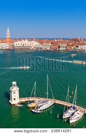 View of small lighthouse and yachts on Grand canal as St Mark's Campanile on background under blue sky in Venice, Italy (vertical composition).