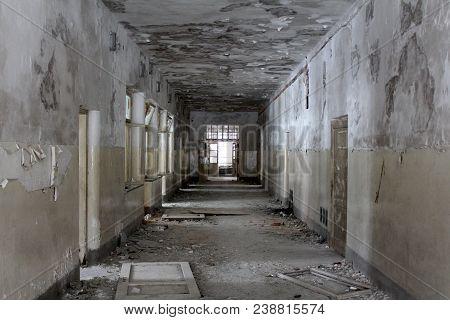 Abandoned building dilapidated corridor with broken doors, windows, glass, wires, bricks and rubble on the floor poster
