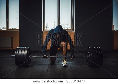 Athletic Man In Jacket With A Hood Waiting Preparing Before Lifting Heavy Barbell. Fitness, Sport, T