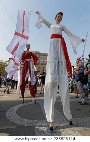 London, Great Britain, April 21, 2018 : Young Women On Stilts Shake English Flags For The Feast Of S
