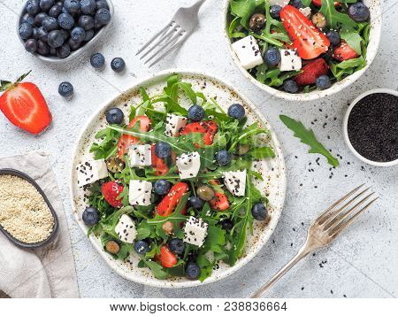 Salad With Arugula, Feta Cheese And Berries - Strawberry, Blueberry, In Craft Plate On Gray Cement B