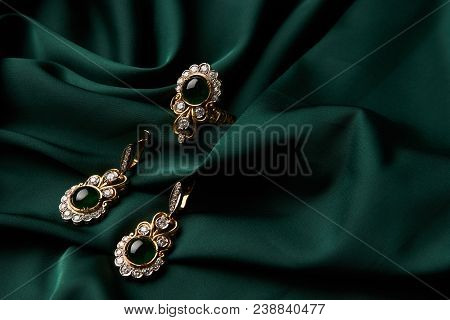 Beautiful Golden Ring And Pair Of Earrings With Green Emerald And Diamonds Gemstones On A Green Sati