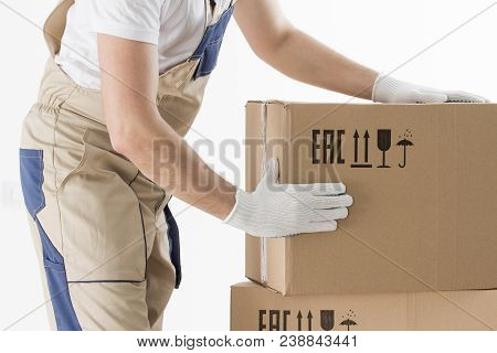 Relocation Services Concept. Mover's Hands In Uniform Carrying Cardboard Box. Loader Puts Cardboard