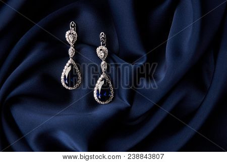 Two Golden sapphire earrings with small diamonds. Pair of platinum earring with sapphire gemstone on blue satin background. Luxury female jewelry, close-up poster