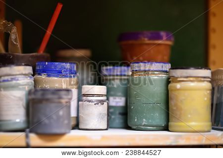 Colorful Cans Of Paint On The Shelf In The Workshop. Paint