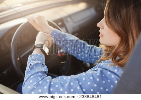 Busy Young Woman Drives Car And Looks At Watch, Stuck In Traffic Jam, Hurries To Work, Being Nervous