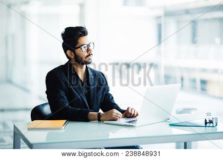 Portrait Of A Busy Indian Guy Multitasking, Taking Notes, Reading Paper, Surfing Internet With Lapto