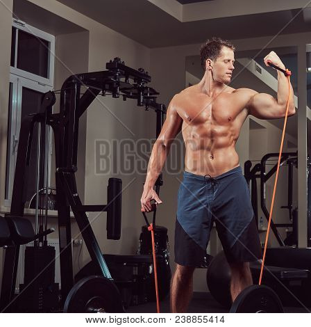 A Muscular Shirtless Athlete Doing Exercise With An Expander In The Gym.