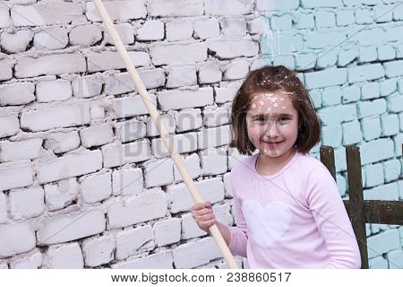 Girl Paints Wall With Roller And Paint In Green Painted Face Paint