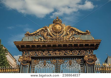"""Detail of golden iron gate and fence lavishly decorated under sunny blue sky in Paris. Known as the """"City of Light"""", is one of the most impressive world cultural center. Northern France. poster"""