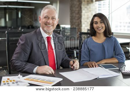 Portrait Of Smiling Experienced Mentor And Young Female Employee. Mid Adult Man In Formal Jacket And